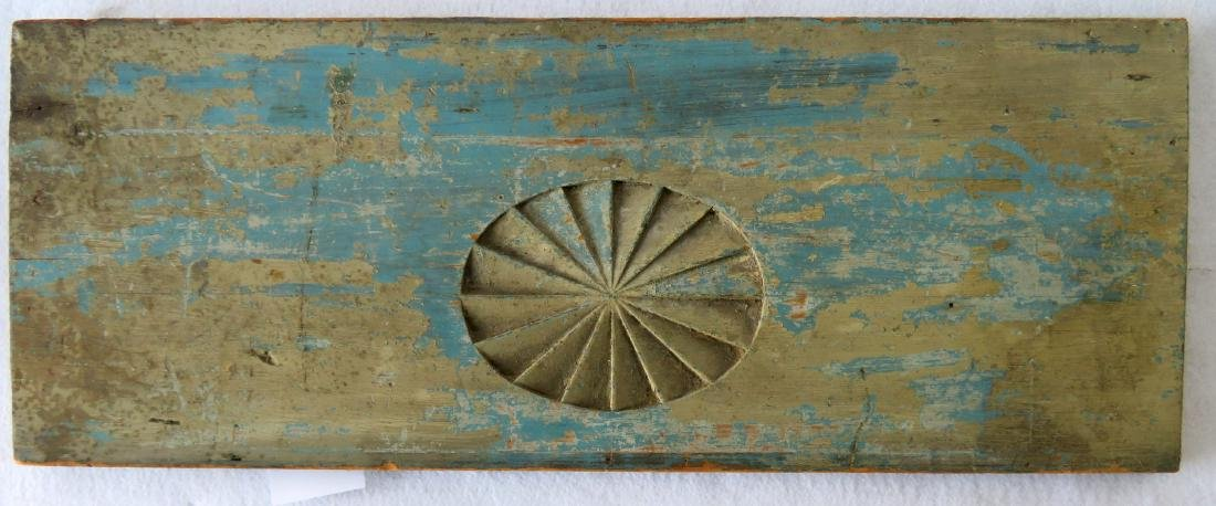 An architectural wooden panel having a carved oval