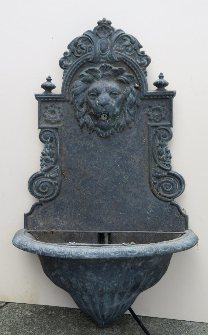 Zinc wall mounted water fountain decorated with scrolls