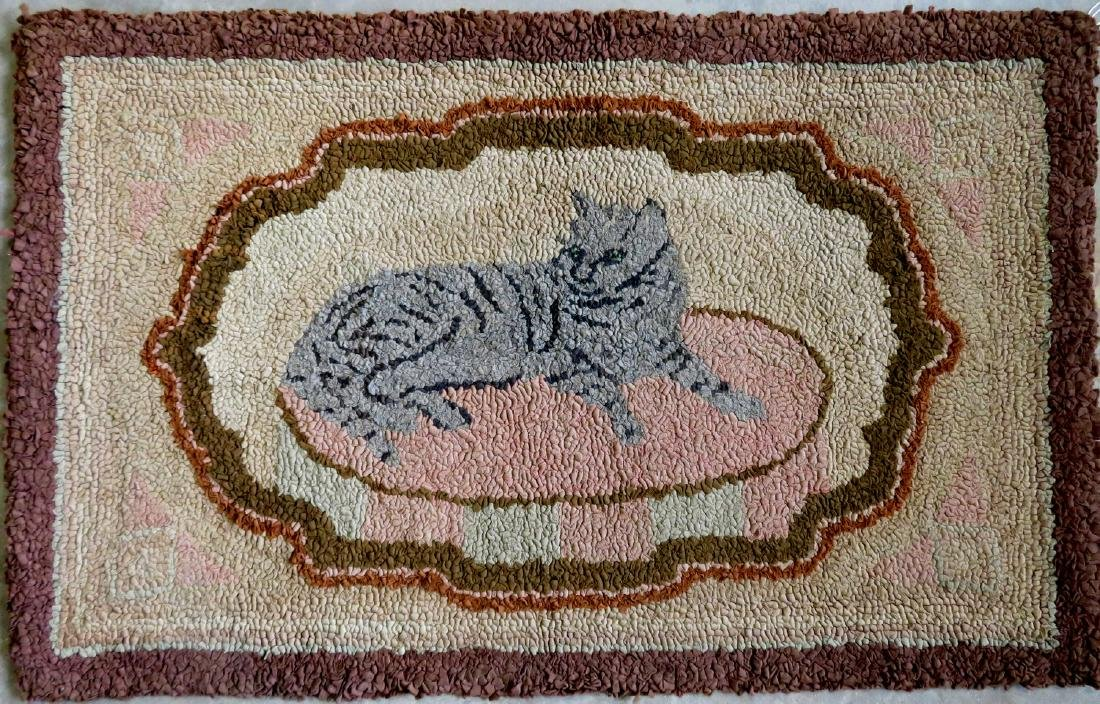 Hooked rug of a gray cat resting on rug, brown border -
