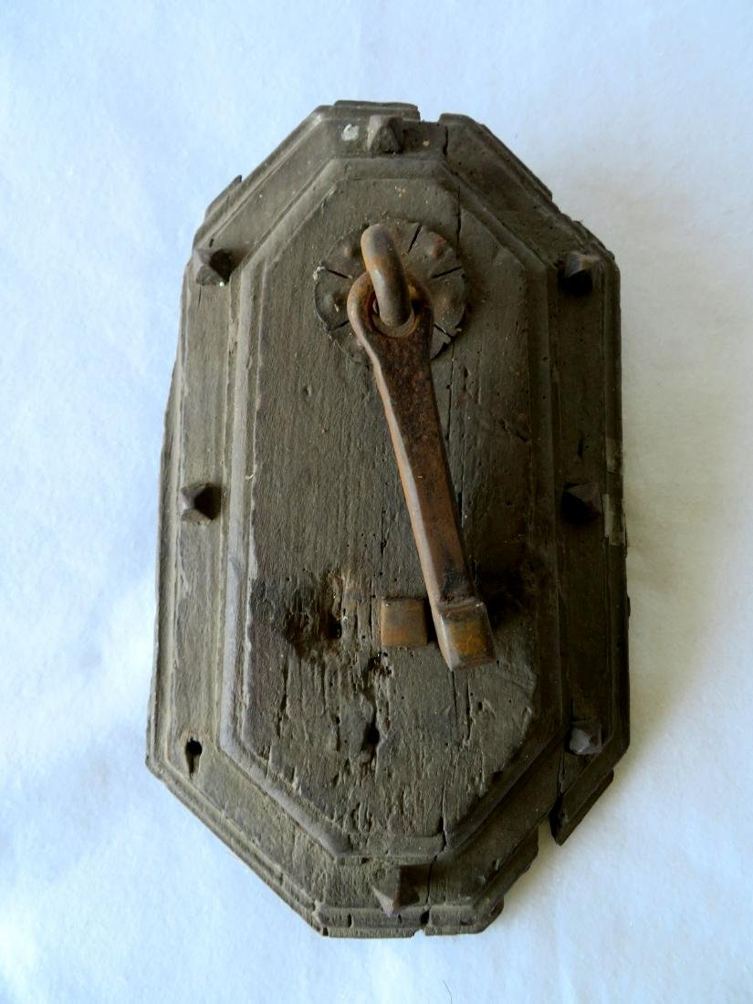 Primitive iron door knocker still mounted to part of an