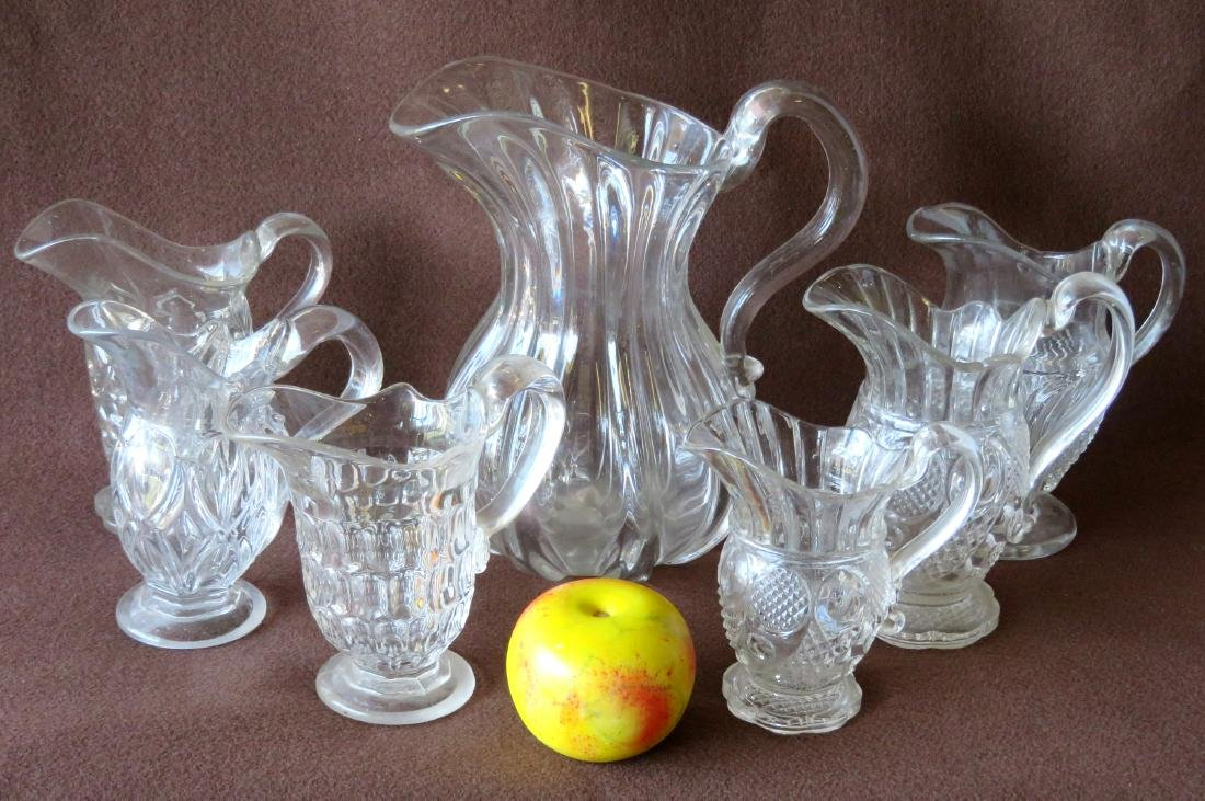 Grouping of 7 early colorless glass pitchers including