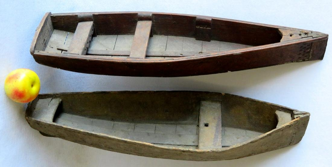 Two handmade wooden rowboats, both with traces of