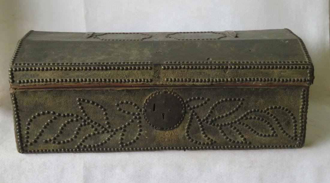 An early leather covered wooden trunk decorated with