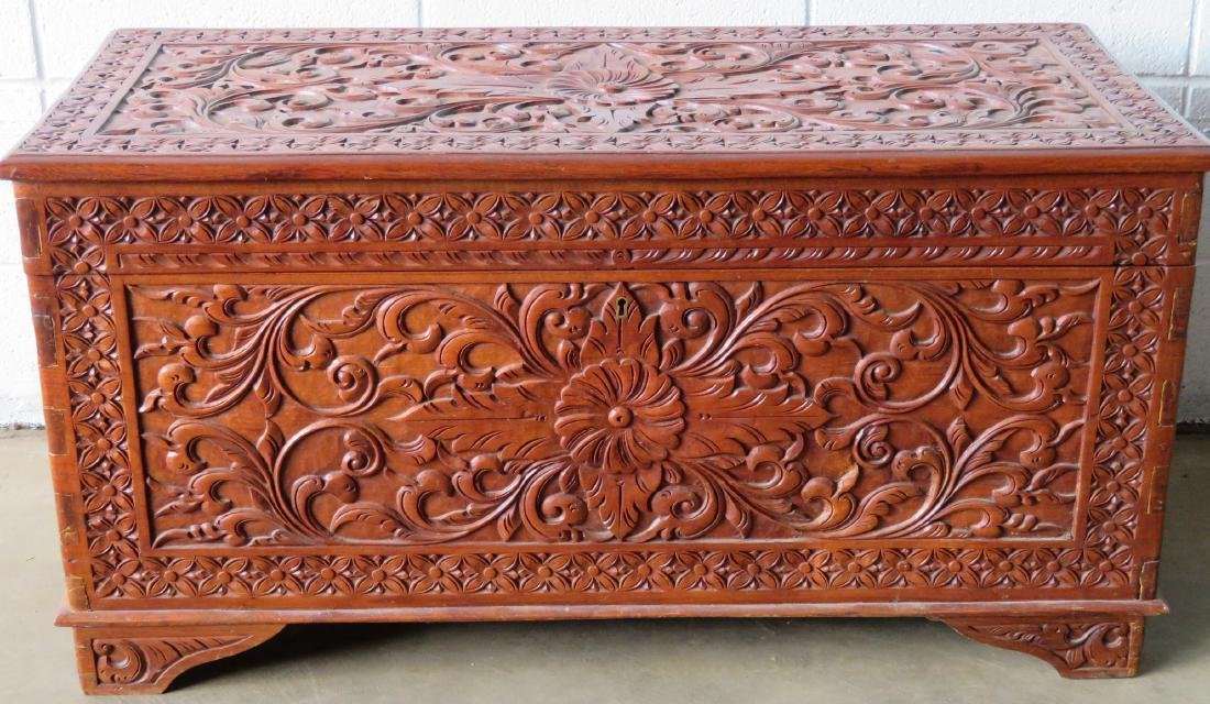 Profusely carved wooden hope chest decorated with