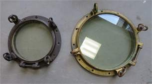 Two brass ship portholes the smaller with natural
