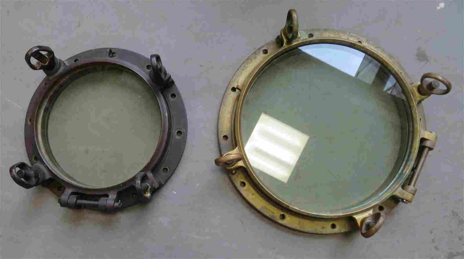 Two brass ship portholes, the smaller with natural