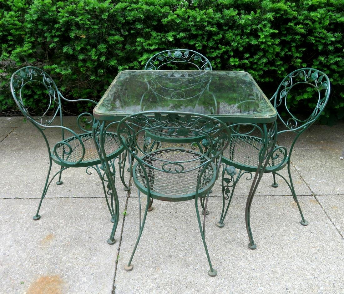 Glass top wrought iron patio table with 4 matching
