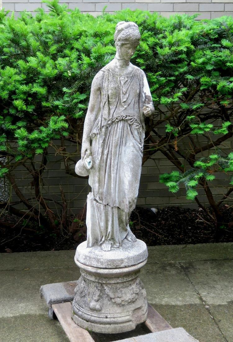 A cast stone garden sculpture/fountain, that depicts a