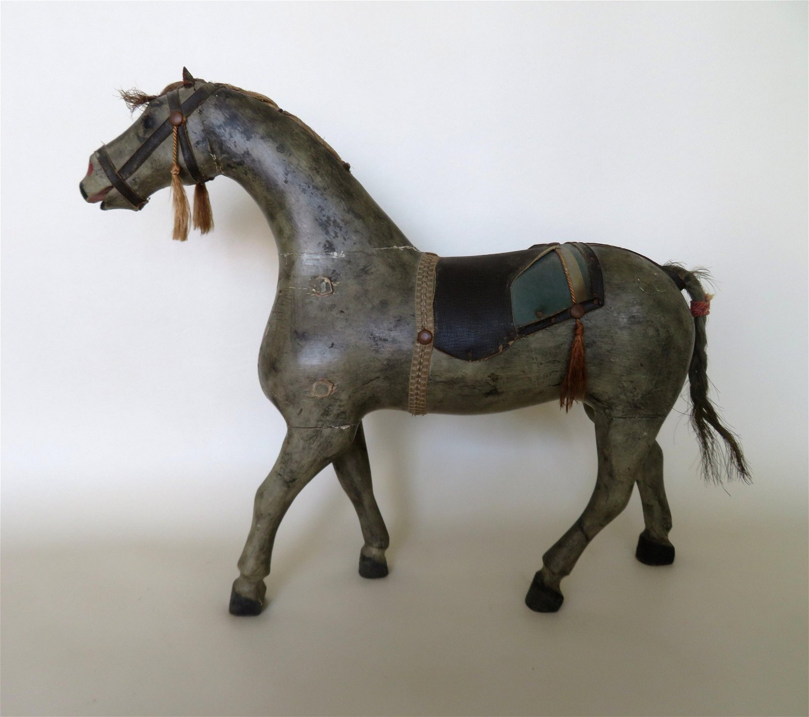 A folk art carved and painted horse with horse hair