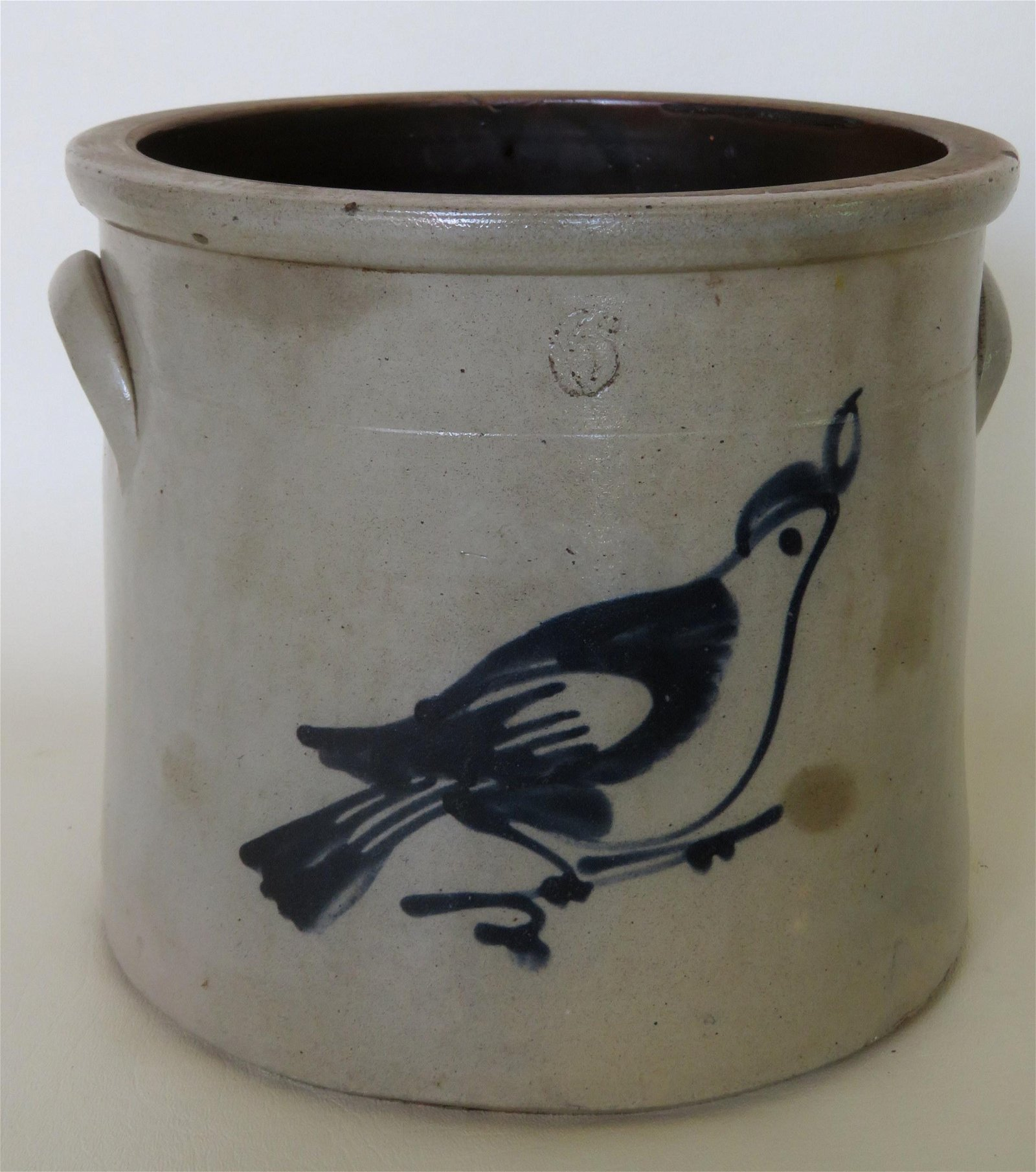 A stoneware crock decorated with a cobalt blue bird on