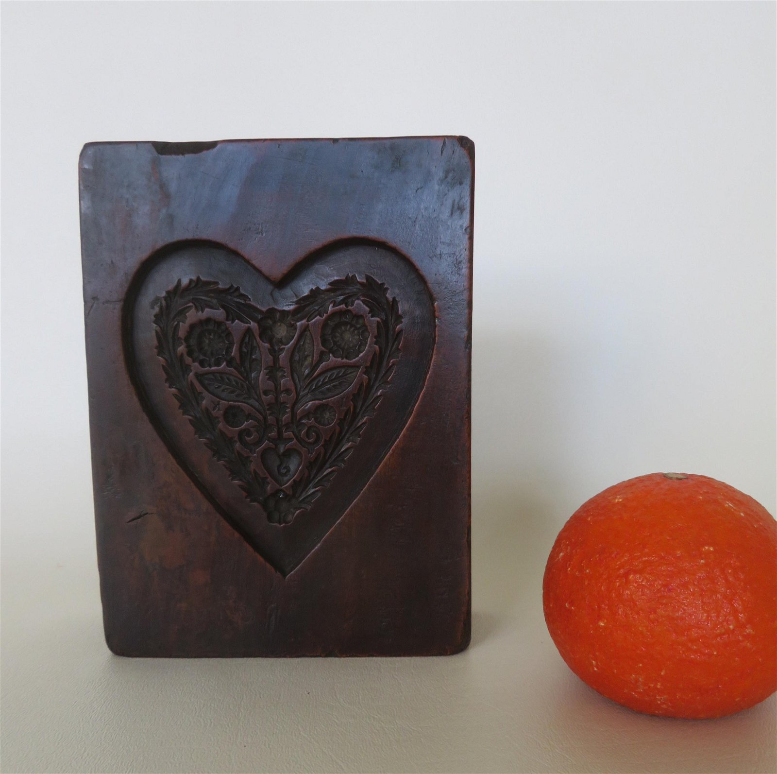 An early mahogany carved cookie mold in the shape of a