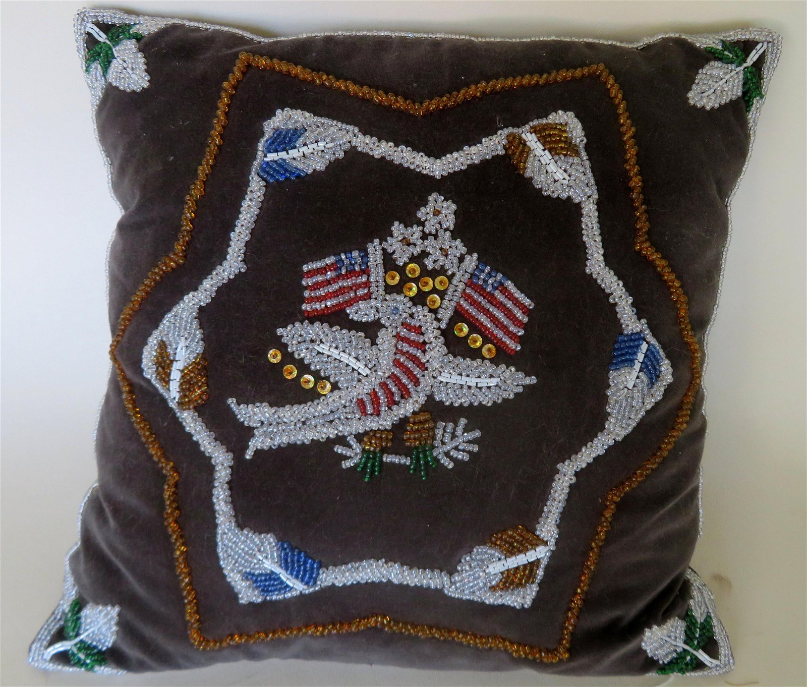 A velvet beadwork pillow, the center decorated by an