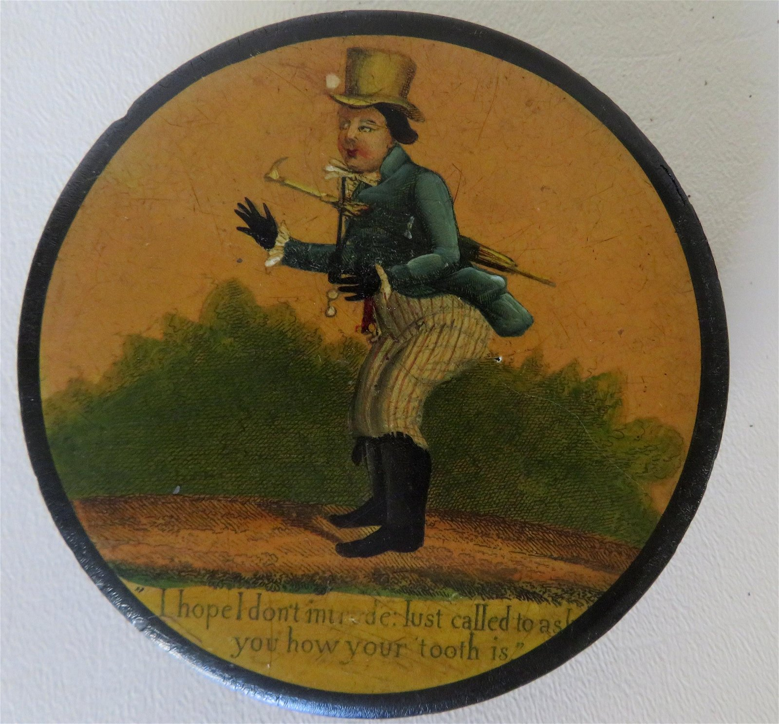 An circular paper mache snuff box with hand painting of