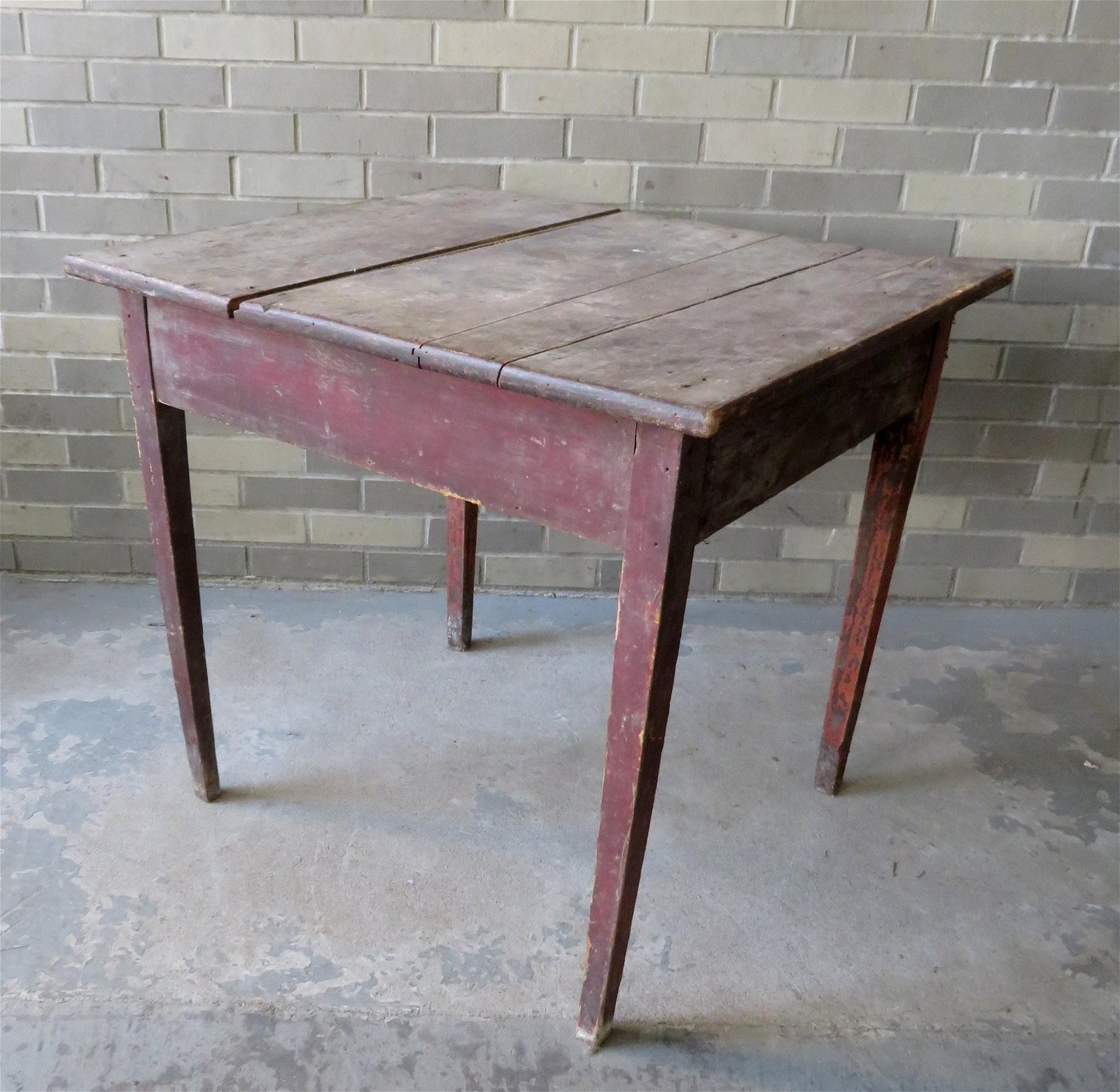 A primitive Hepplewhite tap table with tapered legs,