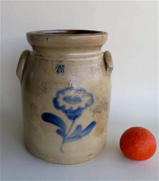 A stoneware crock decorated with a cobalt blue flower,