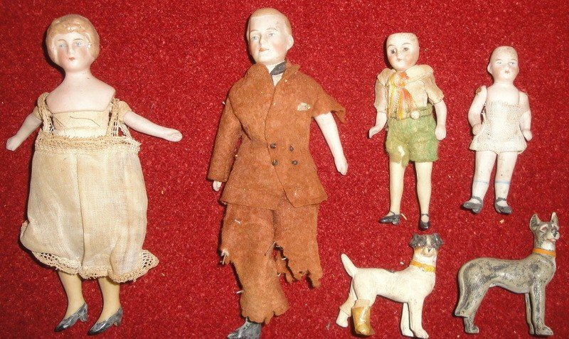 185: Grouping of four miniature porcelain dolls - one w
