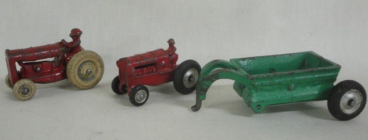 186: Three cast iron farm toys inc. two tractors and ca