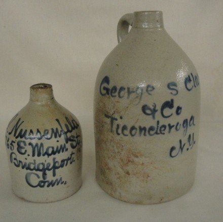 10: Two stoneware country store jugs: one signed in blu
