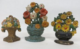 Three Cast Iron Floral Door Stops In Old Paint.