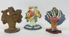 12: Three painted cast iron floral door stops