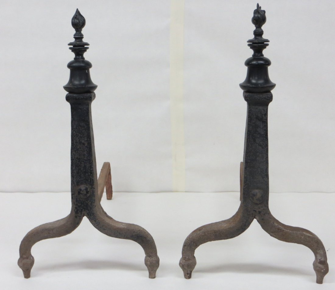 "Pair of cast iron andirons with flame finials. 19.5""H"