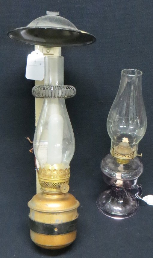 Two oil lamps including one in amethyst color, the