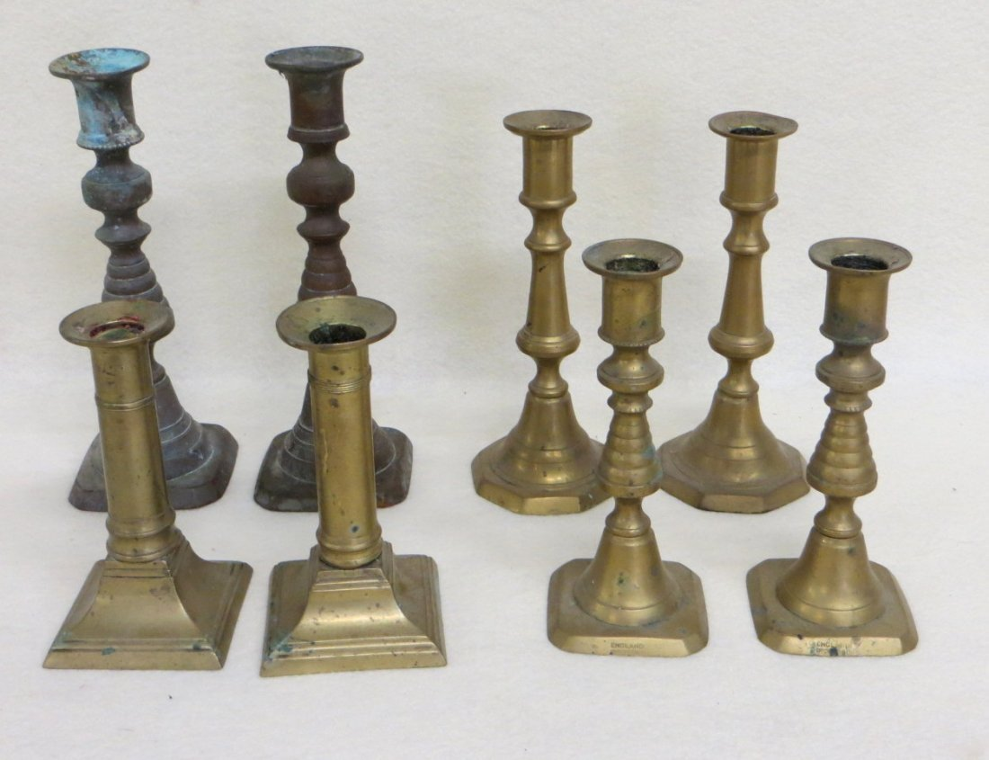 Four pairs of brass pushup candlesticks ranging in size