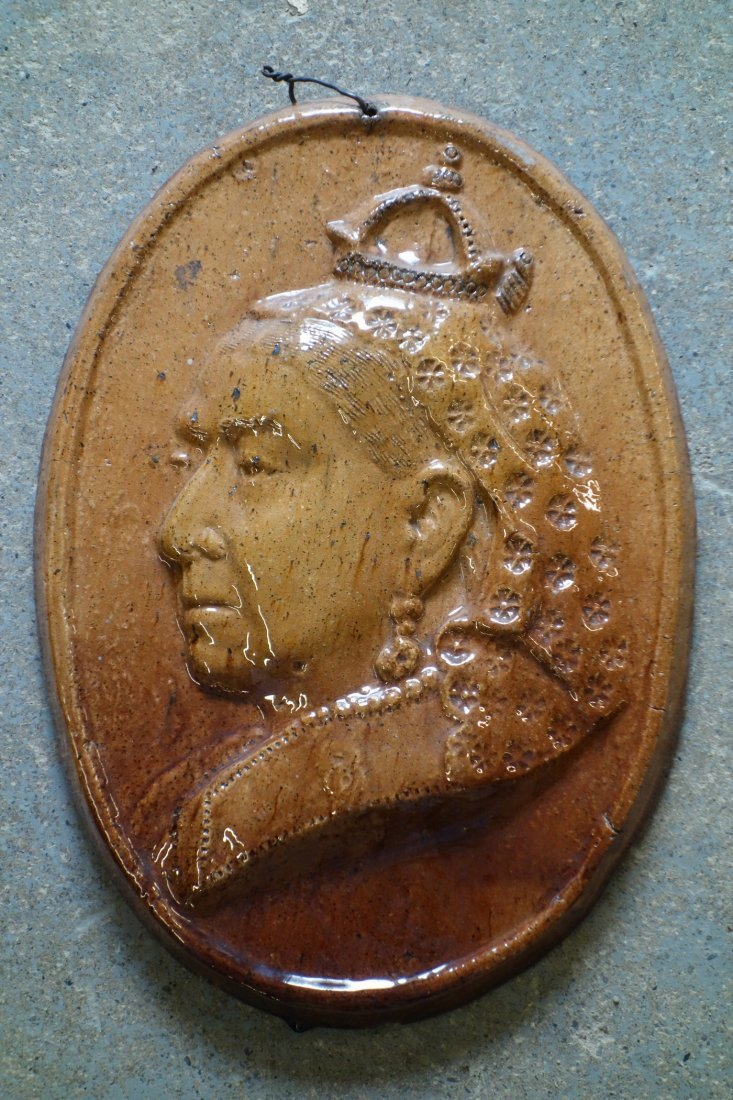 An earthenware wall plaque with sponge brown glaze,