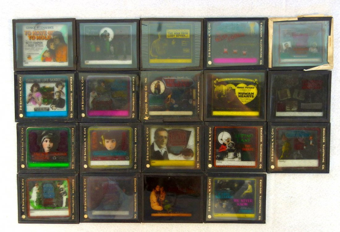Grouping of 19 glass slides of old movie posters some