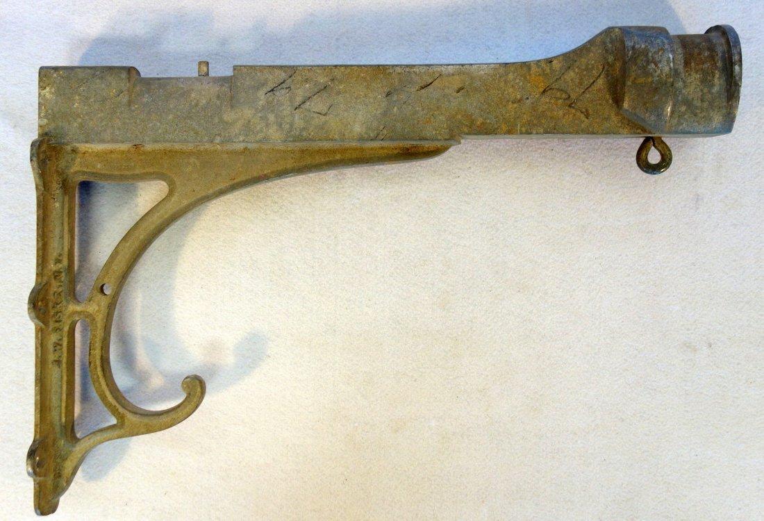 Old cast zinc saddle or sign holder signed J.W. Fiske