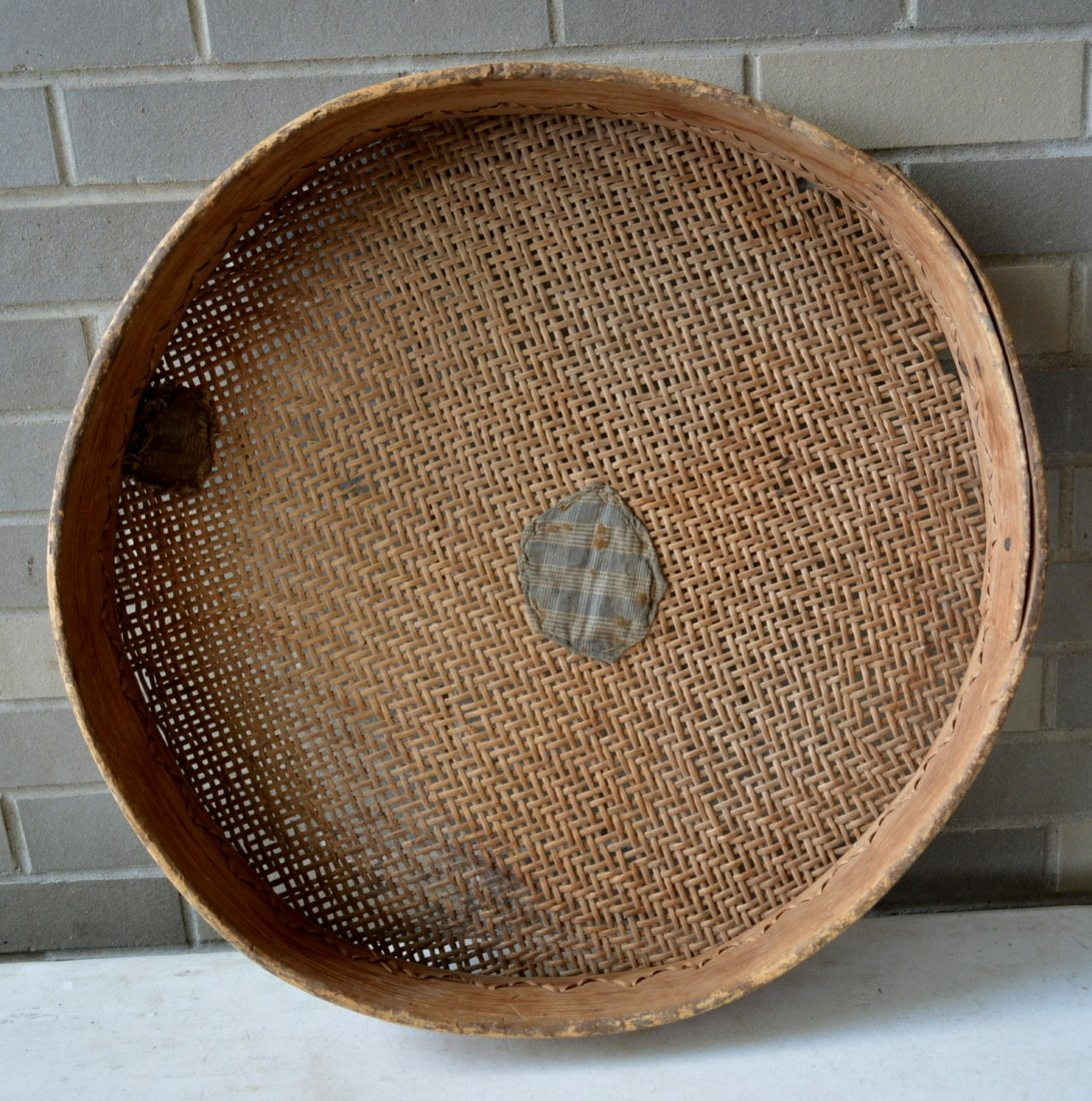 Primitive winnowing basket with homespun repairs to