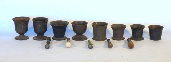 Grouping of 8 early cast iron mortars and 5 pestles.