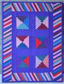 Mounted Amish crib quilt in the log cabin pattern with