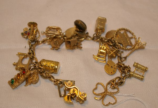 1021: 10 k. Gold charm bracelet with 22 kt. Gold of cha