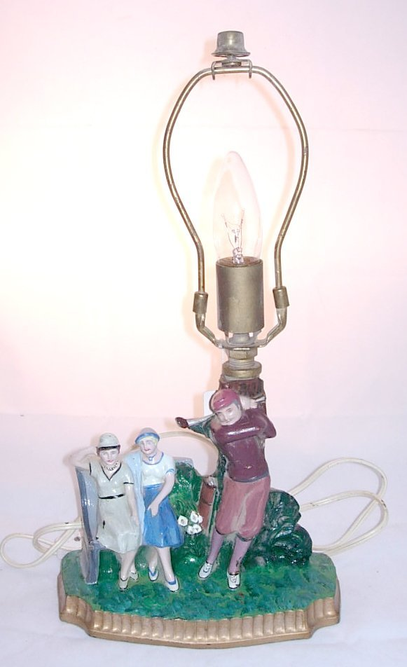 21: White metal lamp depicting a golfer with 2 ladies o