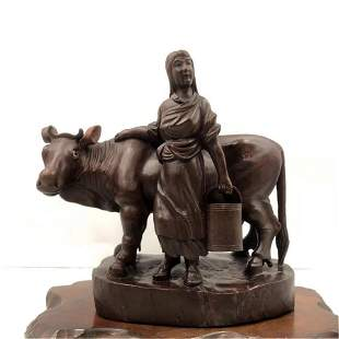 A CHINESE LONGYAN WOOD CARVED LADY AND CATTLE