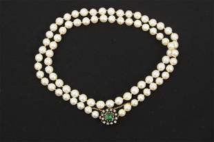 A cutured pearl necklace with an emerald and diamond