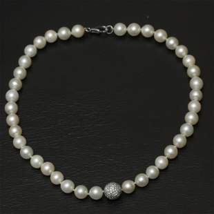 An Akoya cultured pearl necklace with a diamond and