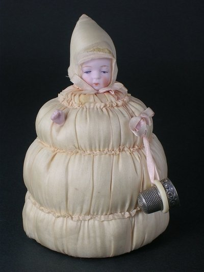 "16E: 5"" PINCUSHION WITH BISQUE BABY HEAD & HANDS"