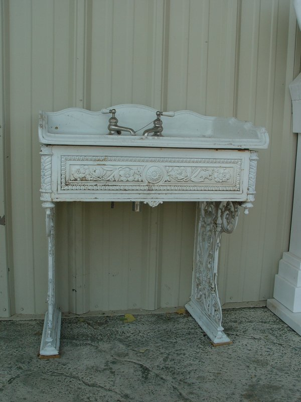 834: CAST IRON VANITY WITH PORCELAIN SINK. SINK HAS CRA
