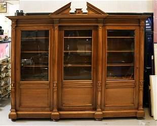 Antique walnut bookcase protected by 3 glazed sliding