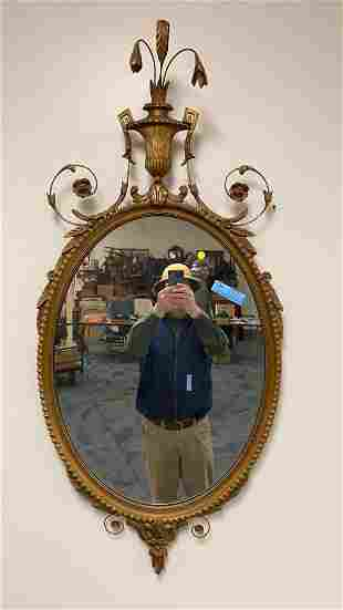 LARGE CARVED OVAL MIRROR WITH CARVED URN AT THE TO