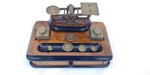 A parcel ebonized burlwood and brass balance scale