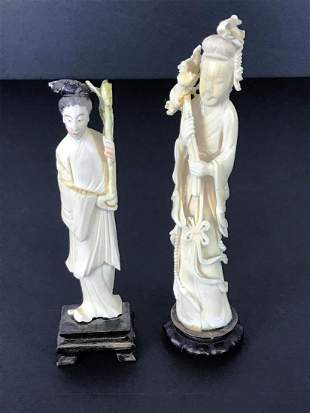 Male and Female carved statues on pedestals