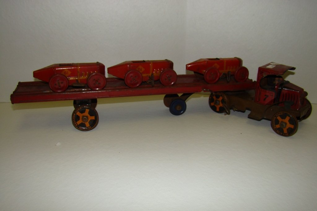 "704: Marx No. 7 tin race car carrier, 22"" long, with th"