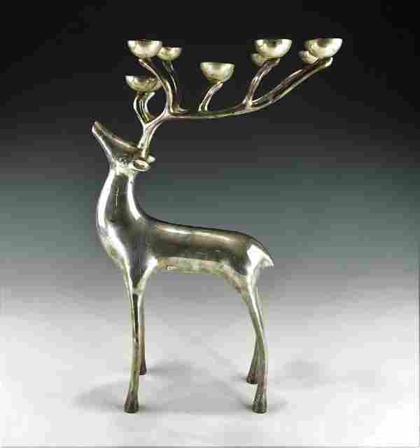 A HEAVY SILVER COLORED DEAR CANDLE HOLDER