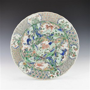 A CHINESE FAMILLE VERTE LARGE PLATE WITH BARBED RIM