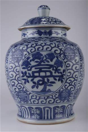 A BLUE-AND-WHITE HAT-COVERED JAR