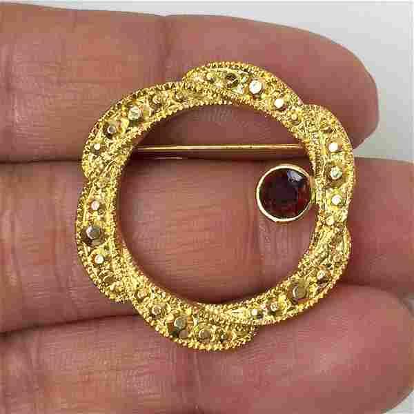 Gold tone textured finish garnet color crystal brooch