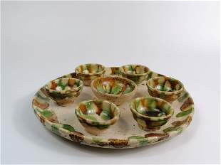 A SANCAI GLAZED POTTERY CIRCULAR TRAY AND SEVEN CUPS